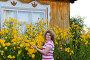 Портрет симпатичной женщины среднего возраста на фоне желтых цветов около деревянного дома, фото № 6692104, снято 31 июля 2014 г. (c) Володина Ольга / Фотобанк Лори