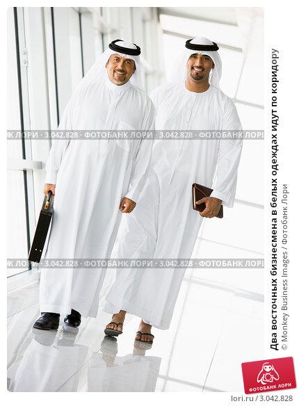 Два восточных бизнесмена в белых одеждах идут по коридору, фото 3042828.