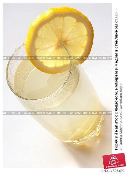 Горячий напиток с лимоном, имбирем и медом в стеклянном стакане на белом...