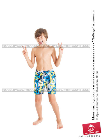 Мальчик подросток в плавках показывает знак Победа и смеется, фото