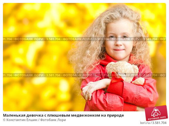 Маленькая девочка с плюшевым медвежонком на природе; фотограф