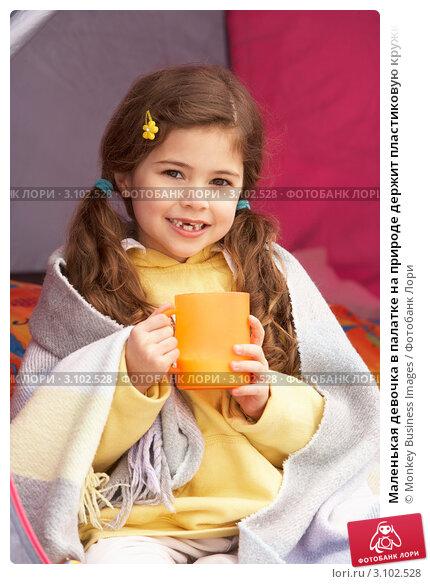 Маленькая девочка в палатке на природе держит пластиковую кружку с