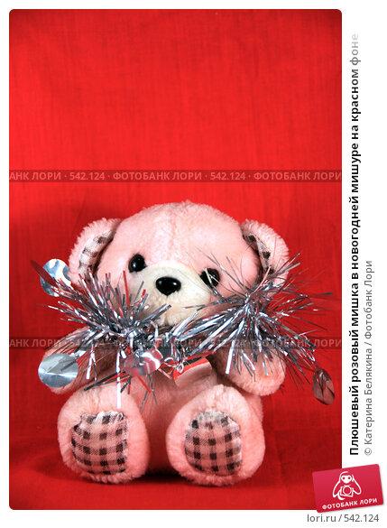 Плюшевый розовый мишка в новогодней мишуре на красном фоне, фото 542124.
