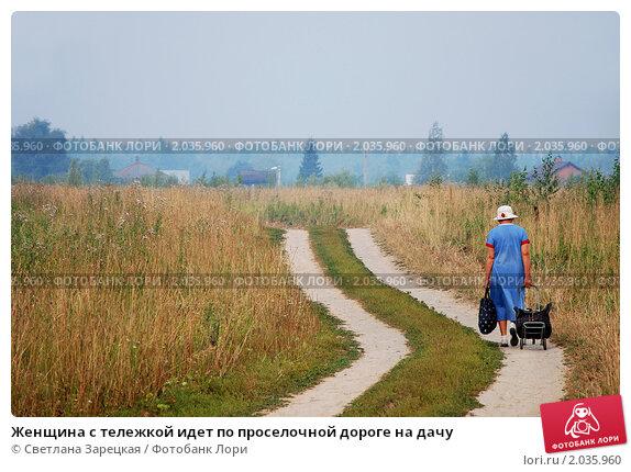 Женщина с тележкой идет по проселочной дороге на дачу...