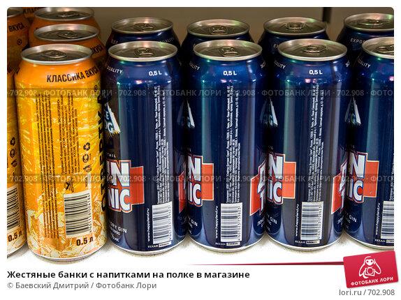 Жестяные банки с напитками на полке в магазине, фото 702908.
