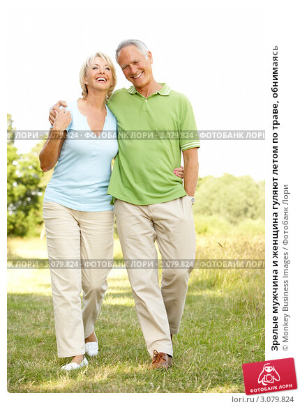 Зрелые мужчина и женщина гуляют летом по траве, обнимаясь, фото 3079824, сн