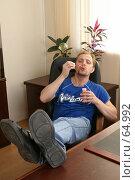 Купить «Молодой мужчина пускает мыльные пузыри в офисе, положив ноги на стол», фото № 64992, снято 22 июля 2007 г. (c) Julia Nelson / Фотобанк Лори