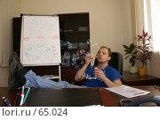 Купить «Молодой человек пускает мыльные пузыри в офисе, положив ноги на стол», фото № 65024, снято 22 июля 2007 г. (c) Julia Nelson / Фотобанк Лори