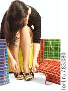 Купить «Девушка с покупками поправляет пряжки на босоножках», фото № 83080, снято 14 мая 2007 г. (c) Андрей Армягов / Фотобанк Лори