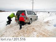Купить «Двое мужчин толкают пробуксовывающий в снегу автомобиль», фото № 201516, снято 9 февраля 2008 г. (c) Сергей Лаврентьев / Фотобанк Лори