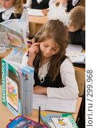 Купить «Первоклассница на уроке отгородилась книгой от соседа», фото № 299968, снято 14 мая 2008 г. (c) Федор Королевский / Фотобанк Лори