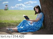 Купить «Читающая в тени дерева девушка с семьей на заднем плане», фото № 314420, снято 24 июня 2007 г. (c) Сергей Байков / Фотобанк Лори