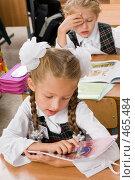 Купить «Первоклассница на уроке разглядывает обложку», фото № 465484, снято 18 сентября 2008 г. (c) Федор Королевский / Фотобанк Лори