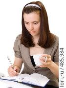 Купить «Девушка держит чашку в руках и продолжает работать», фото № 485984, снято 20 апреля 2008 г. (c) Ольга Красавина / Фотобанк Лори