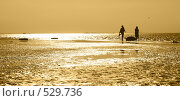Двое мужчин на берегу возле лодки во время заката. Желтая тонировка. Стоковое фото, фотограф Егор Архипов / Фотобанк Лори