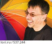 Купить «Смеющийся мужчина на фоне разноцветного зонта», фото № 537244, снято 31 августа 2008 г. (c) Михаил Лавренов / Фотобанк Лори