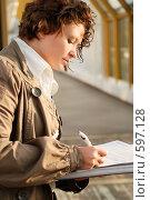 Купить «Молодая девушка, подписывающая документы», фото № 597128, снято 15 ноября 2008 г. (c) Дмитрий Яковлев / Фотобанк Лори
