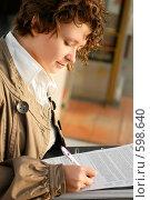 Купить «Молодая девушка, подписывающая документы», фото № 598640, снято 15 ноября 2008 г. (c) Дмитрий Яковлев / Фотобанк Лори