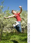 Купить «Девочка прыгает в саду на фоне цветущих яблонь», фото № 602572, снято 3 мая 2008 г. (c) Ирина Игумнова / Фотобанк Лори