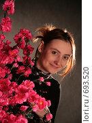 Весна, юная девушка улыбается, выглядывая из-за цветущих веток персика. Стоковое фото, фотограф Natalie Molchanova / Фотобанк Лори