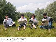 Молодые люди читают газеты, сидя на траве. Стоковое фото, фотограф Losevsky Pavel / Фотобанк Лори