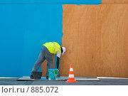 Темнокожий мужчина красит ограждение из фанерных листов в синий цвет (2009 год). Редакционное фото, фотограф Сергей Шустов / Фотобанк Лори