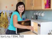 Купить «Девушка ставит стакан воды в микроволновку», фото № 994760, снято 24 июля 2009 г. (c) Гладских Татьяна / Фотобанк Лори