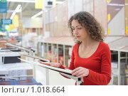 Купить «Девушка в магазине выбирает керамическую плитку», фото № 1018664, снято 20 декабря 2008 г. (c) Losevsky Pavel / Фотобанк Лори