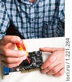 Человек с отверткой нремонтирует электронный прибор (2009 год). Редакционное фото, фотограф Виктор Шмыголь / Фотобанк Лори