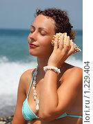 Купить «Красивая женщина слушает ракушку на берегу моря», фото № 1229404, снято 13 июля 2009 г. (c) Losevsky Pavel / Фотобанк Лори