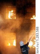 Купить «Пожарный тушит пожар водой из брандспойта. На втором этаже здания человек яростно пытается спастись», фото № 1283588, снято 7 декабря 2009 г. (c) Татьяна Белова / Фотобанк Лори