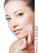 Купить «Красивая девушка наносит крем на щеку», фото № 1343964, снято 21 ноября 2008 г. (c) Валуа Виталий / Фотобанк Лори