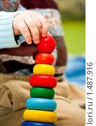 Рука маленького ребенка держит цветную пирамидку. Стоковое фото, фотограф Анна Макеичева / Фотобанк Лори