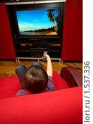 Купить «Ребенок смотрит телевизор, сидя на диване. Держит пульт в руке.», фото № 1537336, снято 8 марта 2010 г. (c) Куликова Татьяна / Фотобанк Лори