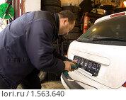 Мужчина электрическим шуруповертом закрепляет на автомобиле рамку для государственных регистрационных знаков (2010 год). Редакционное фото, фотограф Ольга Спиркина / Фотобанк Лори