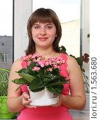 Купить «Девушка держит горшок с цветущим каланхоэ», фото № 1563680, снято 18 марта 2010 г. (c) Alechandro / Фотобанк Лори
