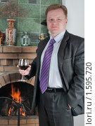 Купить «Мужчина в модном костюме с бокалом красного вина у камина», фото № 1595720, снято 19 марта 2010 г. (c) Федор Королевский / Фотобанк Лори