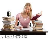 Купить «Красивая девушка сидит за столом среди книг на белом фоне», фото № 1675512, снято 3 февраля 2010 г. (c) Мельников Дмитрий / Фотобанк Лори