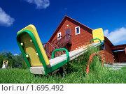 Купить «Детские качели на фоне деревянного дома», фото № 1695492, снято 7 июня 2009 г. (c) Дмитрий Ощепков / Фотобанк Лори