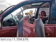 Жёлтый трактор в окне красной разбитой машины на свалке. Стоковое фото, фотограф Евгений Волдаев / Фотобанк Лори