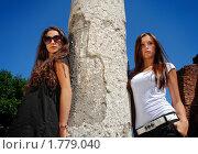 Две молодые брюнетки возле каменной колонны. Стоковое фото, фотограф Андрей Цалко / Фотобанк Лори