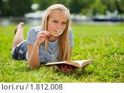 Купить «Красивая девушка лежит на траве в парке с книгой и яблоком», фото № 1812008, снято 9 июня 2010 г. (c) Мельников Дмитрий / Фотобанк Лори