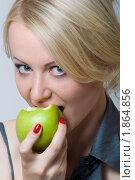 Девушка блондинка откусывает зеленое яблоко. Стоковое фото, фотограф Лысиков Евгений / Фотобанк Лори