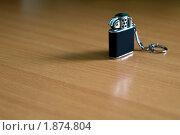 Чёрная бензиновая зажигалка на дешёвом коричневом столе. Стоковое фото, фотограф Андрей Комаров / Фотобанк Лори