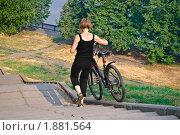 Купить «Женщина спускает велосипед по лестнице», эксклюзивное фото № 1881564, снято 26 июля 2010 г. (c) Алёшина Оксана / Фотобанк Лори