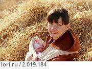 Купить «Молодая мама с ребенком в слинге отдыхает на стоге сена», фото № 2019184, снято 26 сентября 2010 г. (c) Иванюшин Виталий / Фотобанк Лори