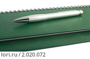 Купить «Металлическая ручка, лежащая на зеленом блокноте», фото № 2020072, снято 3 октября 2010 г. (c) Andrey Eremin / Фотобанк Лори