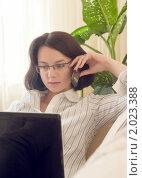 Купить «Девушка в очках с телефоном и ноутбуком на диване», фото № 2023388, снято 7 сентября 2010 г. (c) Никита Жигелев / Фотобанк Лори