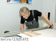 Мастер-багетчик на резаке подрезает типографское изделие для последующей установки в раму.Багетная мастерская. Стоковое фото, фотограф игорь иванов / Фотобанк Лори