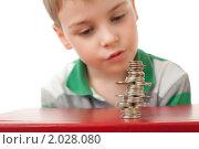 Купить «Мальчик смотрит на стопку монет», фото № 2028080, снято 9 марта 2010 г. (c) Losevsky Pavel / Фотобанк Лори